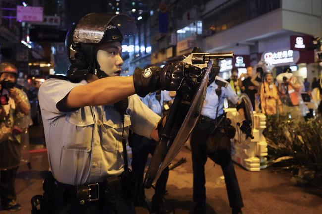 A policeman points a weapon during a protest in Hong Kong on Sunday