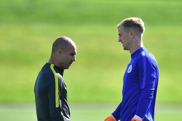 Pep Guardiola, left, talks to Joe Hart during a training session