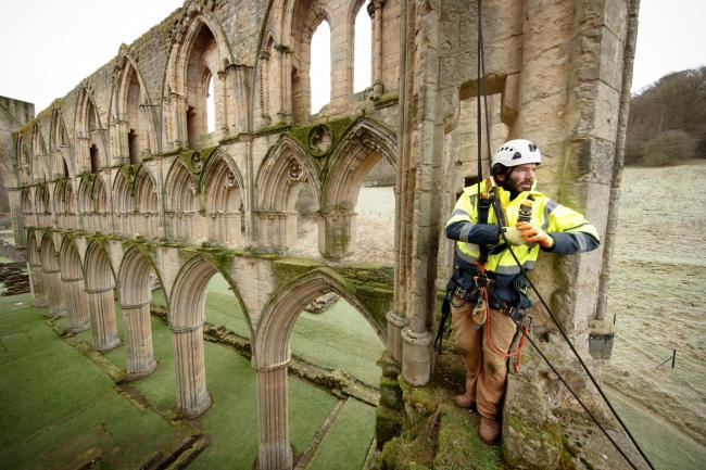 Stonemason James Preston from SSH Conservation surveys Rievaulx Abbey in North Yorkshire