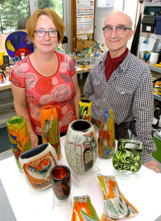 Stourbridge News: Left to right - Natasha George, co-director of the glass festival, and glass artist Vic Bamforth with some of his work. Buy photo: 261242K