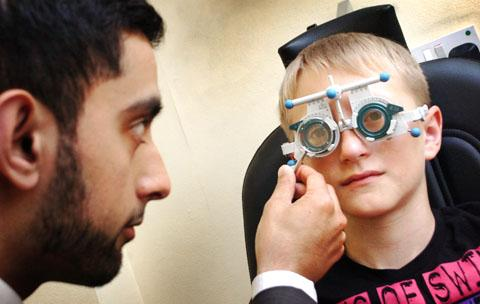 Qadir Baz tests eyes of Pavel Udaloi, aged 11. Buy photo: 341202L