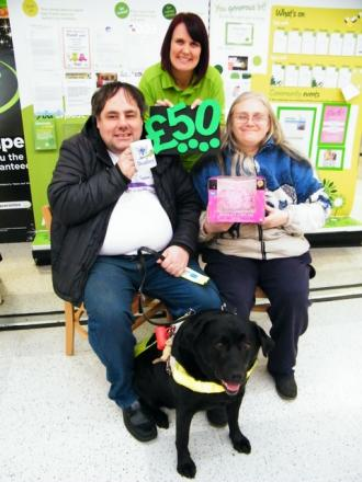 Ken and Tracy McClymont and Haf their guide dog, with Lisa Southall, Merry Hill Asda Communi