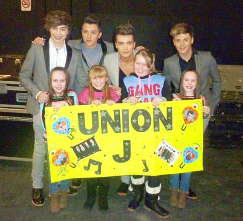 Caitlin Smart (aged eight) Bryany Palmer (aged eight), Georgie Palmer (aged 11), Ellie Smart (aged eight) show Union J their handmade poster.