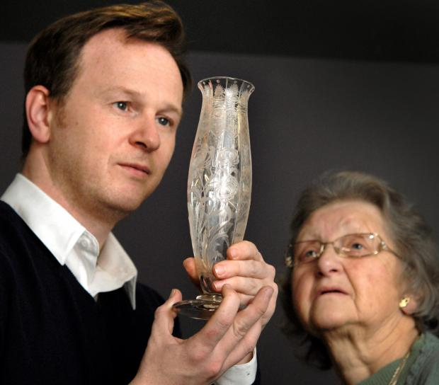 Antiques Roadshow star Will Farmer from Fieldings Auctioneers and Margaret Tatler from Stourbridge with a vase by her grandfather - renowned glass engraver William Kny. Buy photo: 031418L