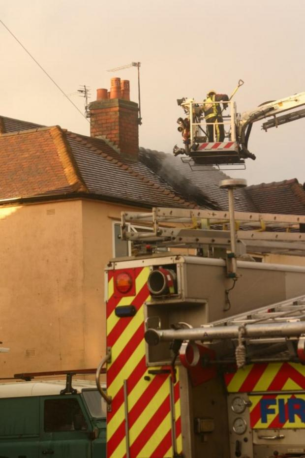 Stourbridge News: Fire fighters in action after lightening strike sparks blaze in Wollescote - picture by Shannon Radford.