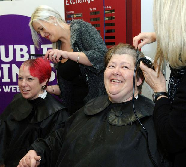 Lisa 'Tink' Cope, left, having her hair shaved by hairdresser Catherine O'Rourke, and Deborah Smith - having her locks chopped off by hairdresser Pam McBride. Buy photo: 061408LA