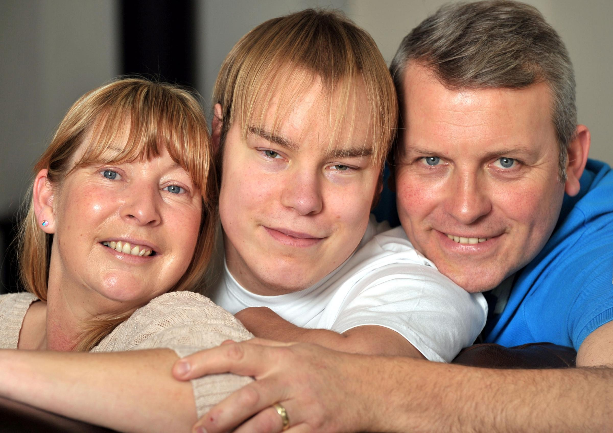 Jake Woolfenden, middle, with his mum and dad, Bridgette and Adrian. Buy this photo: 061413RS.