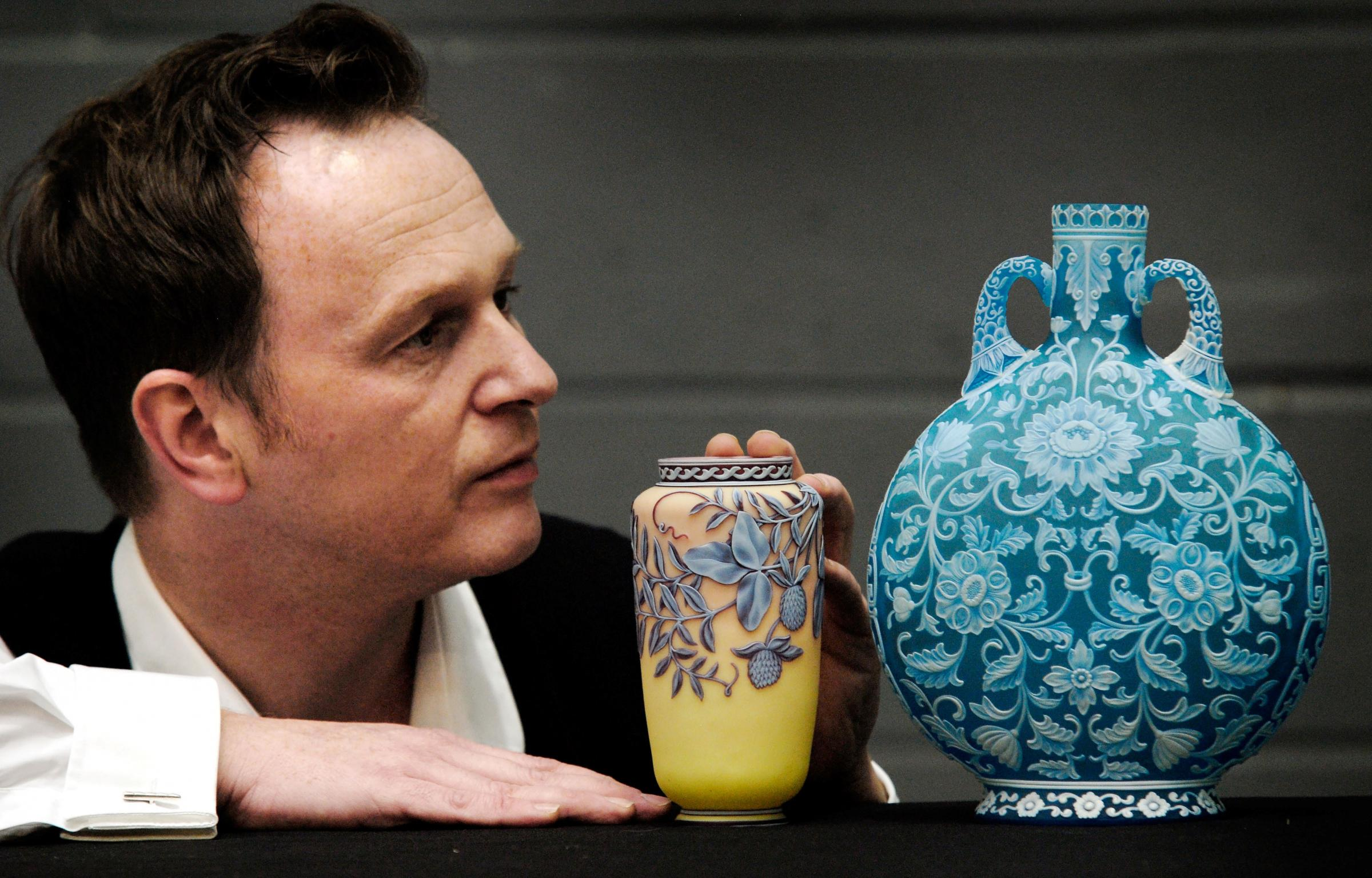 Auctioneer Will Farmer with a Queen's Burmese cameo glass vase and blue cameo moon flask, both by Thomas Webb & Sons. Buy photo: 101409L