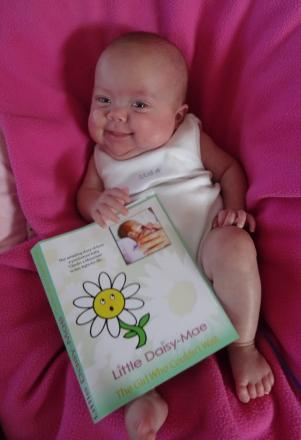 Daisy-Mae with a mock-up copy of the book.