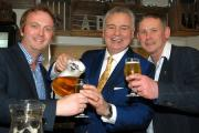 Eamonn Holmes pours drinks for Chris Sadler, left, and Ian King, right.