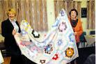 Picture shows Jean right handing over the quilt to Evadne Wright.