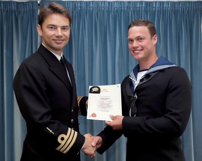 Stourbridge Navy diver Mitchell Bowen receiving his certificate from Commander Simon Pressdee