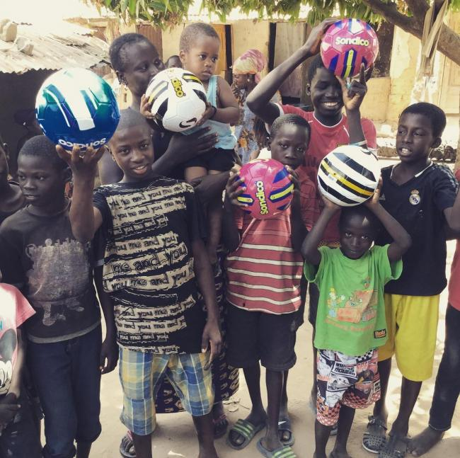Distributing footballs at Kutosilo village. Photo: Project Gambia