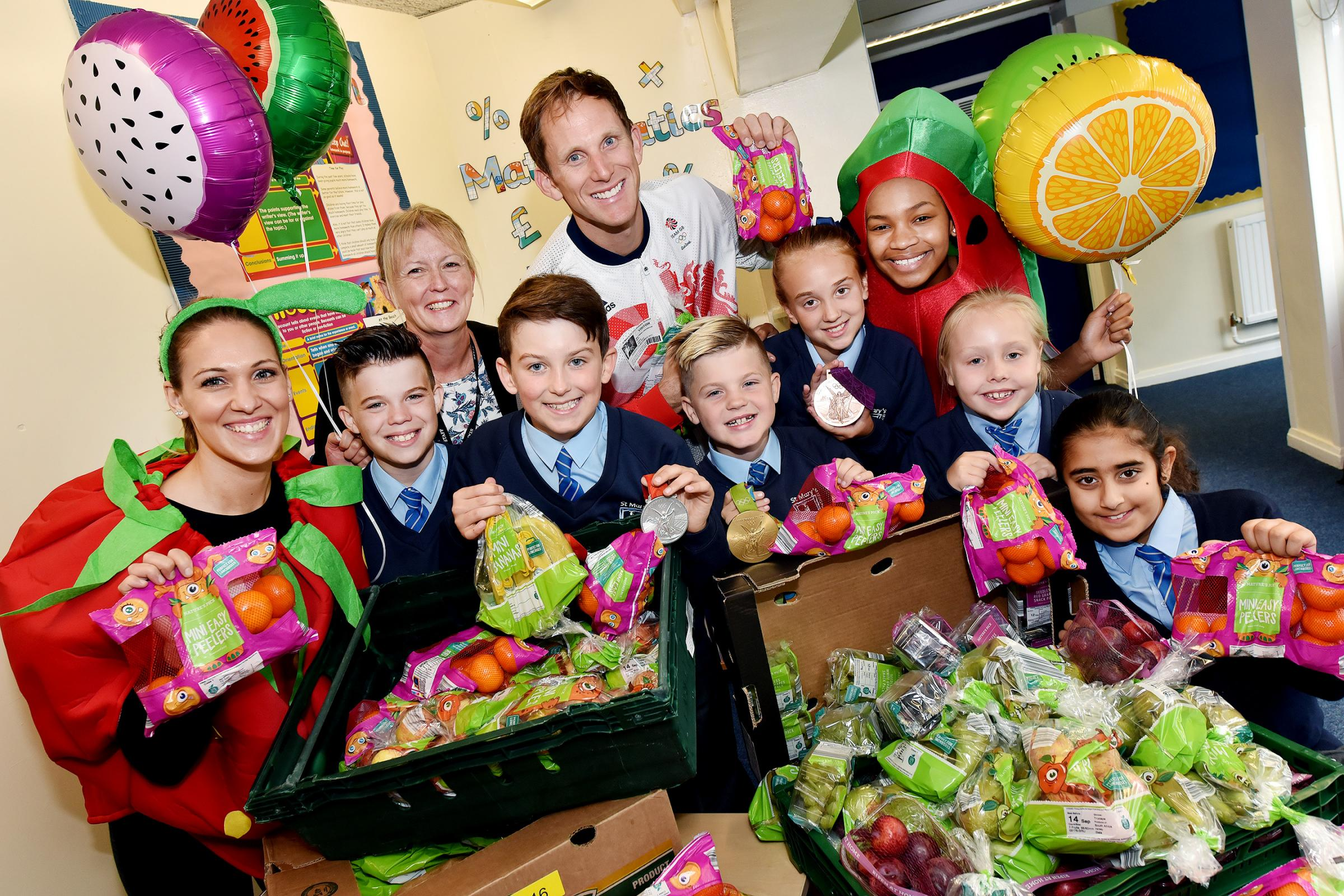 Olympic medallist Matthew Langridge, headteacher Beverley Roberts and children from St Mary's C of E Primary School celebrate Aldi's Super 6 donation