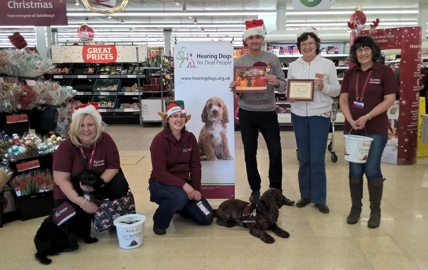 Hearing Dogs for Deaf People volunteers present deputy store manager Mark Cooper and colleague Julie Bate, with a photo and the birth certificate of hearing dog pup Willow, who has been sponsored through fundraising in store