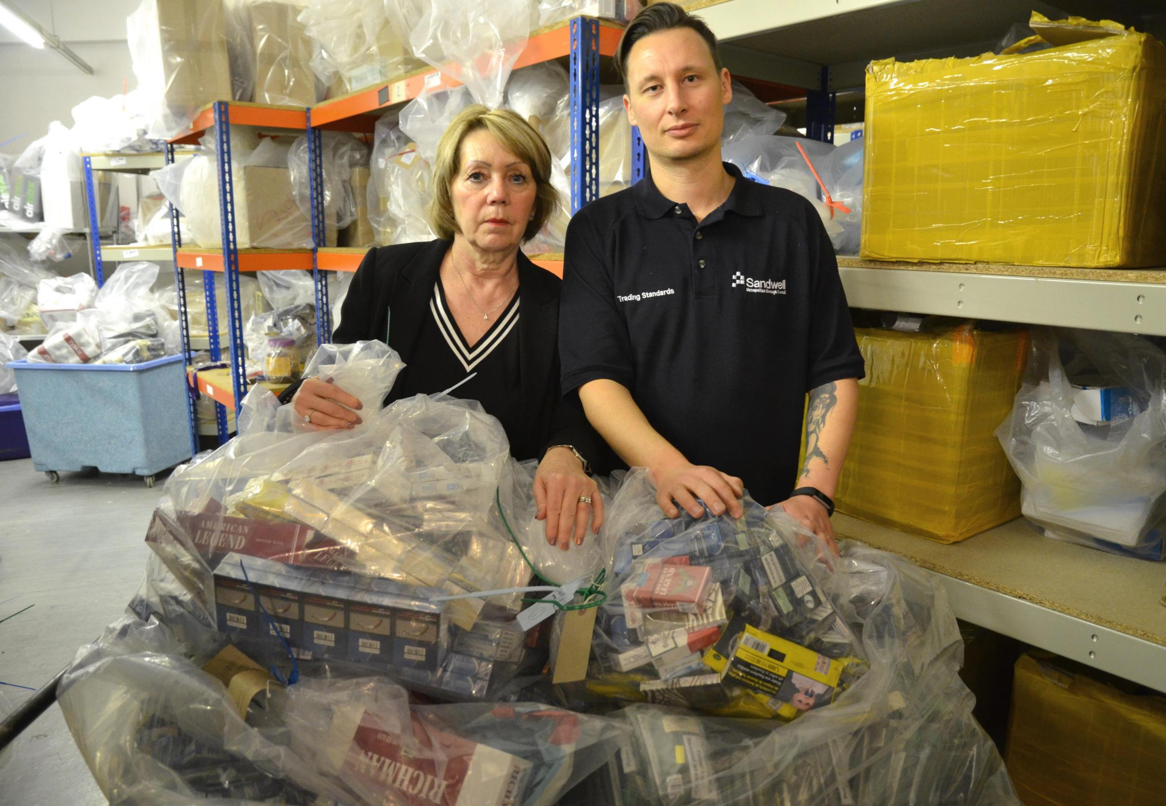 Cabinet member for public health and protection Councillor Elaine Costigan and Mark Beesley from Sandwell Trading Standards with some of the seized items.