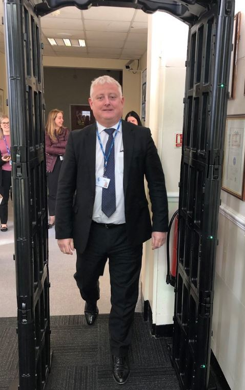 Headteacher Gareth Lloyd walking through the knife arch. Pic - Stourbridge Police