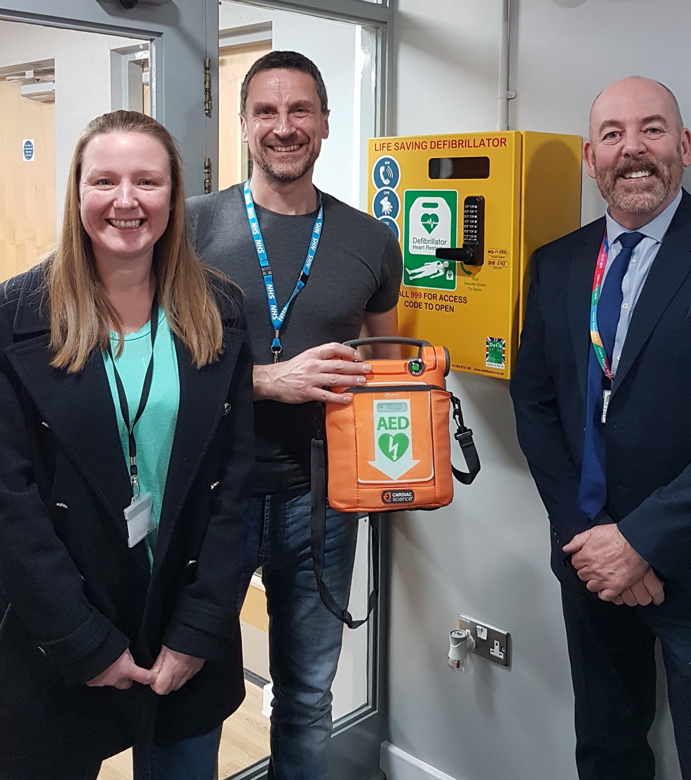 Cllr Kerry Lewis at the school with the new life-saving piece of kit, with Paul Grove (of FastAid Black Country) and headteacher Keith Butler.