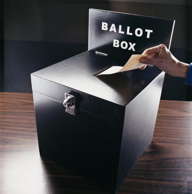 Man Inserting Voting Paper into a Ballot Box.
