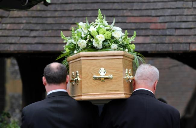 IMAGE: A coffin being led into a funeral ceremony.